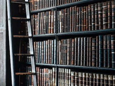 Shelves of older historical books with ladder.