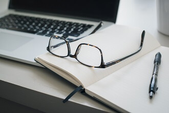 A pair of black glasses rest on an open notebook with a pen lying next to the glasses. The background features an open laptop.