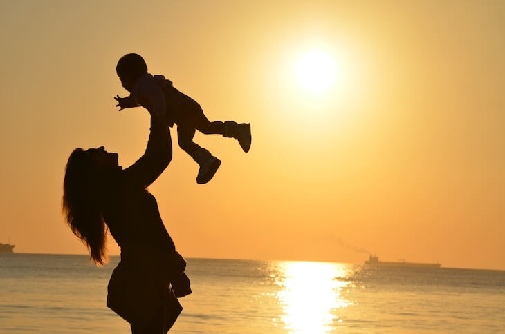Life Events Targeting - Silhouette mother and baby at ocean sunset